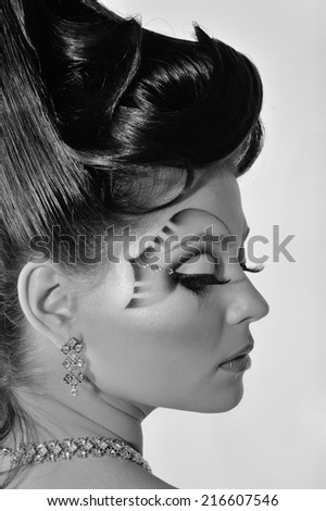 Portrait of a woman on a light background.Body Art.makeup.hairstyle.Black-and-white photo.