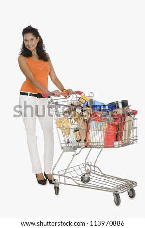 Portrait of a woman pushing a shopping cart - stock photo
