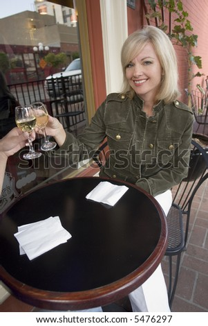 Portrait of a woman raising her wine glass with a friend