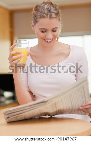 Portrait of a woman reading the news while drinking orange juice in her kitchen - stock photo
