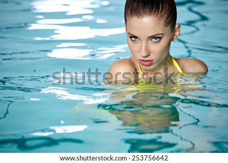 Portrait of a woman relaxing in swimming pool - stock photo