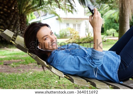 Portrait of a woman relaxing outdoors with mobile phone and earphones - stock photo
