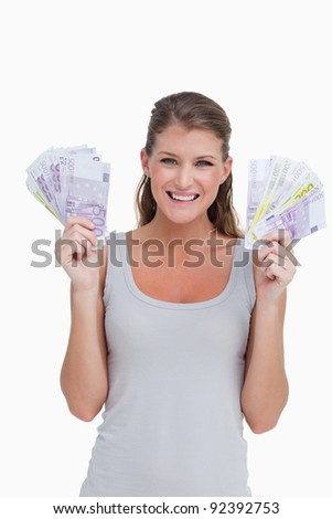 Portrait of a woman showing bank notes against a white background - stock photo