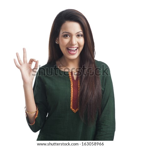 Portrait of a woman showing ok sign and smiling - stock photo