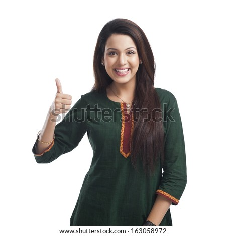 Portrait of a woman showing thumbs up sign and smiling - stock photo