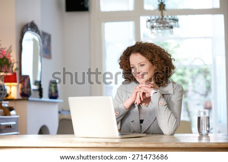 Portrait of a woman sitting at home and looking at computer - stock photo
