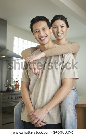 Portrait of a woman sitting on countertop and embracing man from behind - stock photo