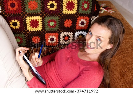 Portrait of a woman sitting on sofa and writing in book - stock photo