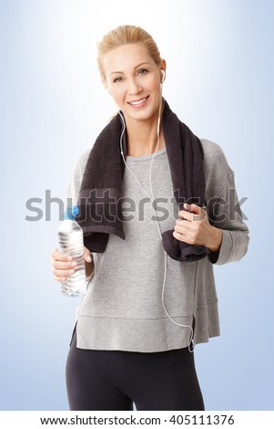 Portrait of a woman standing with a towel around her neck holding a water bottle in her hand.  - stock photo