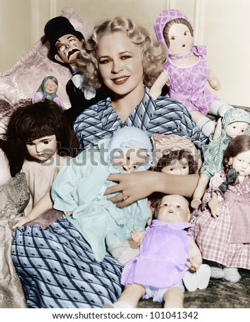 Portrait of a woman surrounded by dolls and smiling - stock photo