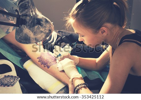 Portrait of a woman tattoo master showing a process of creation tattoo on a hand under the lamp light. - stock photo
