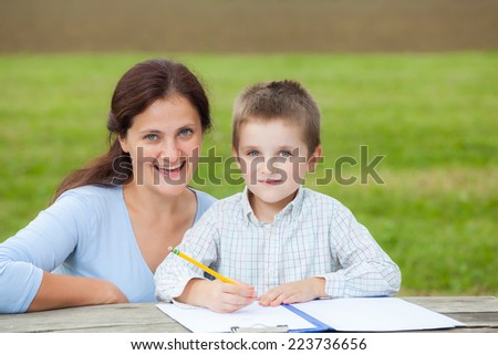 Portrait of a woman teacher or mom and a little young boy in white shirt writing or drawing with a pencil on a sheet of paper on wood table in the park  - stock photo