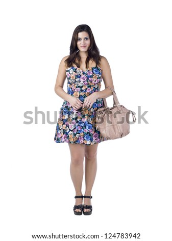 Portrait of a woman wearing blue floral summer dress carrying her bag while standing against white background