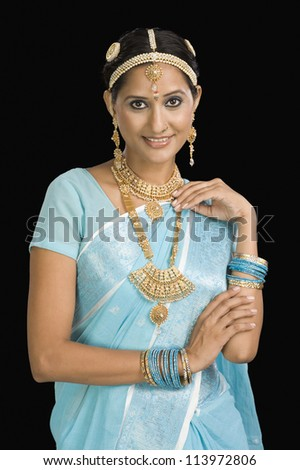 Portrait of a woman wearing jewelry and smiling - stock photo