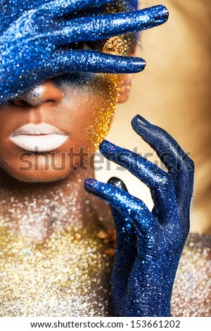 Portrait of a woman who is posing covered with blue and gold paint - stock photo
