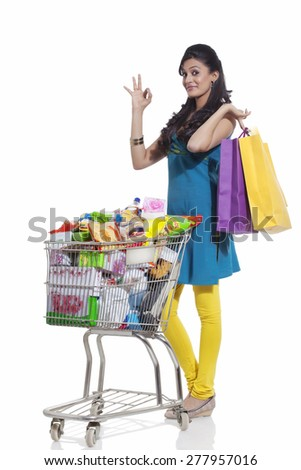 Portrait of a woman with a shopping cart and shopping bags giving ok sign - stock photo