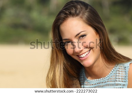 Portrait of a woman with a white teeth and perfect smile outdoors - stock photo