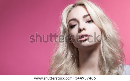 Portrait of a woman with beautiful eyes and blonde hair on a pink background - stock photo