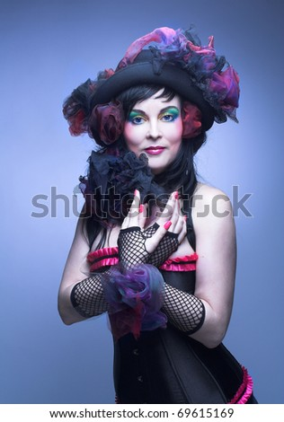 Portrait of a woman with creative make-up and in black hat