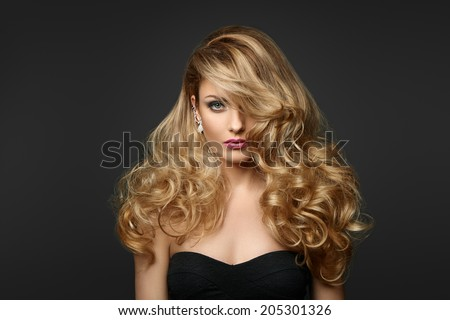 Portrait of a woman with curly hair on a gray background - stock photo