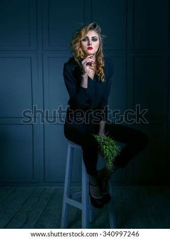Portrait of a woman with flowers. Fashionable ladies. Red lips, blue eyes, green lily of the valley bouquet. Toned image. Females model sitting on a bar stool against the dark wall. Fashion concept. - stock photo