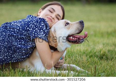 Portrait of a woman with her beautiful dog lying outdoors. Training the dog - stock photo