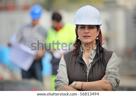 Portrait of a woman with safety helmet crossing her arms - stock photo