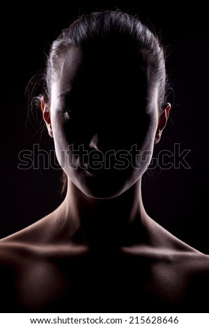portrait of a woman with the face in shadow on a dark background - stock photo