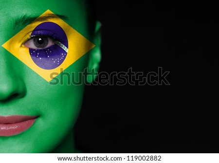 Portrait of a woman with the flag of the Brazil painted on her face - stock photo