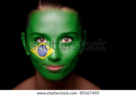 Portrait of a woman with the flag of the Brazil painted on her face. - stock photo