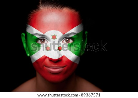Portrait of a woman with the flag of the Burundi painted on her face. - stock photo