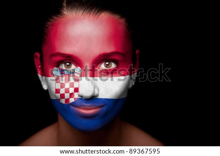 Portrait of a woman with the flag of the Croatia painted on her face. - stock photo