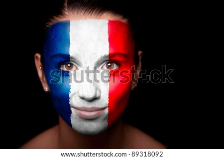 Portrait of a woman with the flag of the France painted on her face. - stock photo