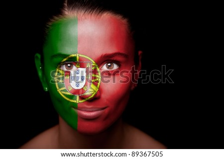 Portrait of a woman with the flag of the Portugal painted on her face. - stock photo
