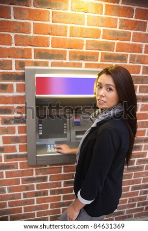 Portrait of a woman withdrawing cash at an ATM