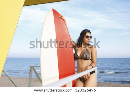 Portrait of a women in swimsuit holding surfboard with copy space for your brand while preparing for swimming, young female with beautiful body relaxing after surfing in the sea in sunny summer day