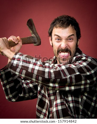 portrait of a woodcutter attacking with his ax - stock photo