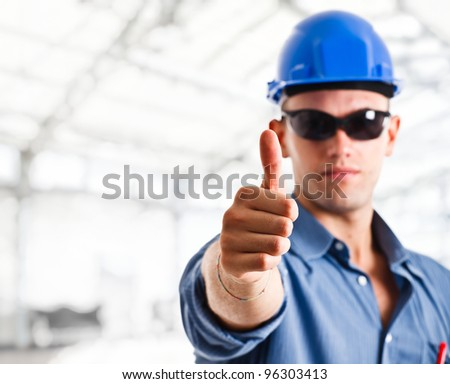 Portrait of a worker doing thumbs up sign - stock photo