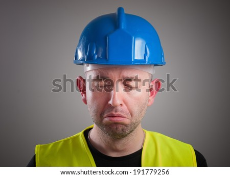 Portrait of a worker expressing negativity and sad, isolated on dark background