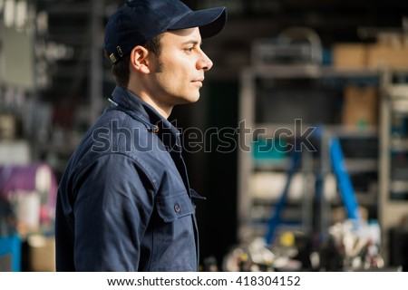 Portrait of a worker in his factory - stock photo