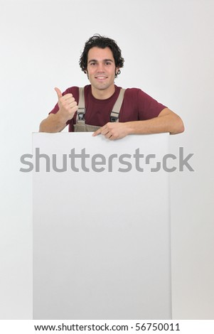 Portrait of a worker in overalls with a white panel - stock photo