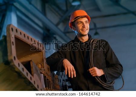 Portrait of a worker in the helmet near the turbine. - stock photo