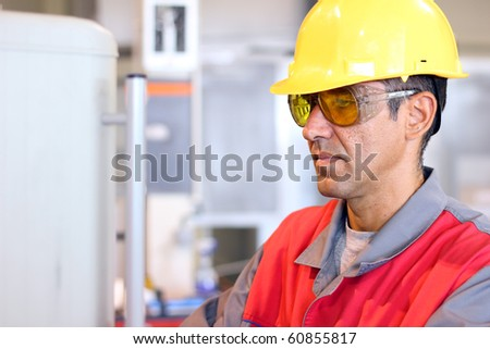 Portrait of a worker wearing protective helmet and safety glasses. CNC machine operator. Industrial worker at work. - stock photo