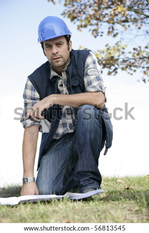 Portrait of a worker with safety helmet crouching - stock photo
