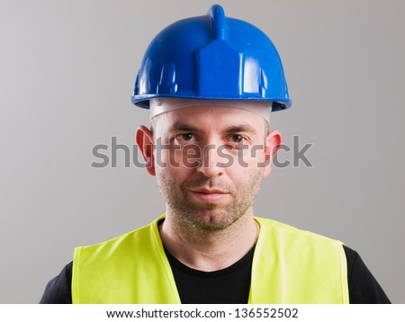 Portrait of a worker with serene expression and isolated on dark background - stock photo
