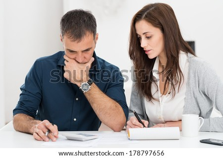 Portrait Of A Worried Couple Calculating Financial Budget - stock photo
