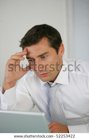 Portrait of a worried man in front of a computer - stock photo