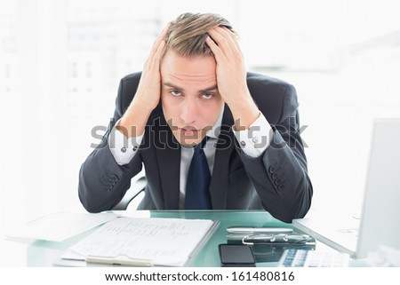 Portrait of a worried young businessman sitting at office desk - stock photo