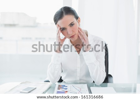 Portrait of a worried young businesswoman with graphs sitting at office desk - stock photo
