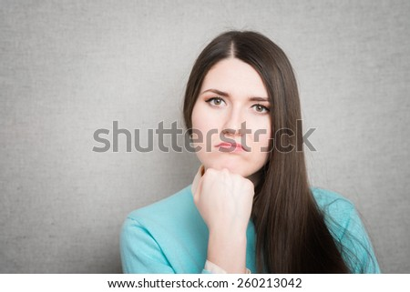 portrait of a worried young woman with a pensive gesture - stock photo